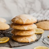 four stacked glazed lemon cookies on a cooling rack