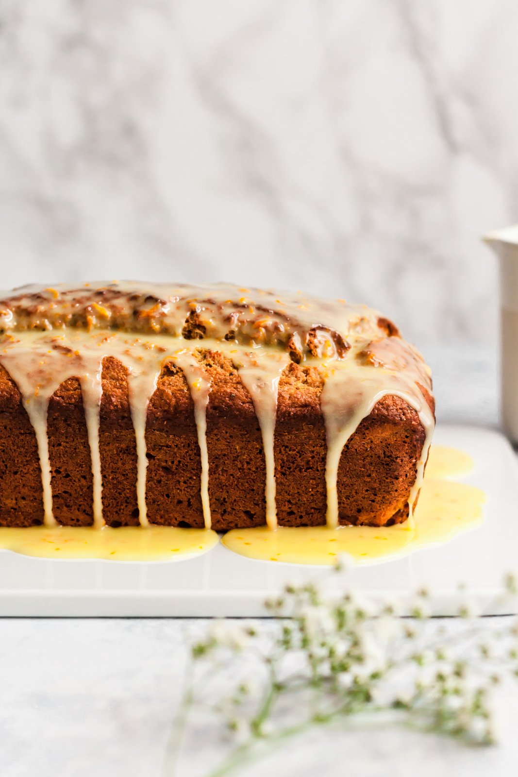 photo of orange bread on a cutting board with glaze on top