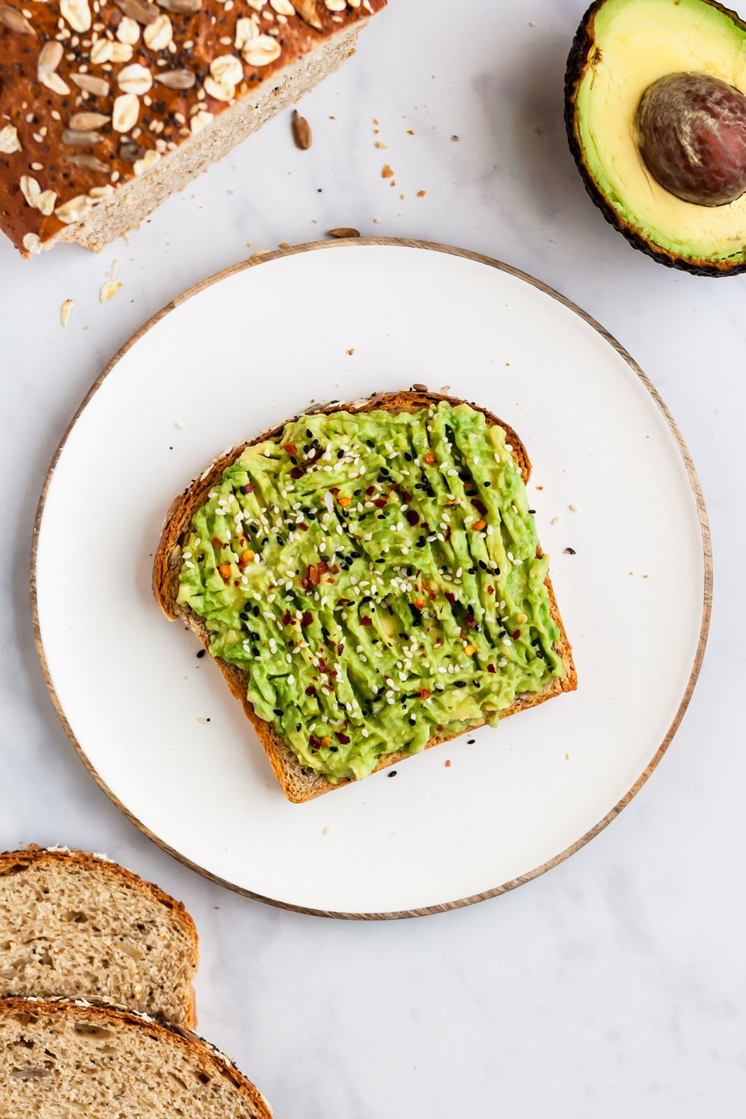 slice of homemade sandwich bread on a plate with mashed avocado on top