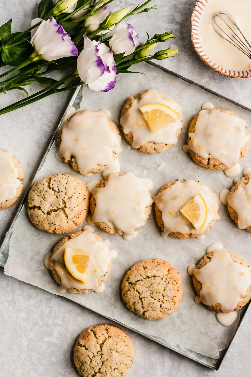 paleo lemon poppy seed cookies on a baking tray next to a bunch of flowers
