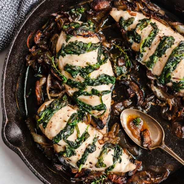 three spinach stuffed chicken breasts in a skillet with a spoon