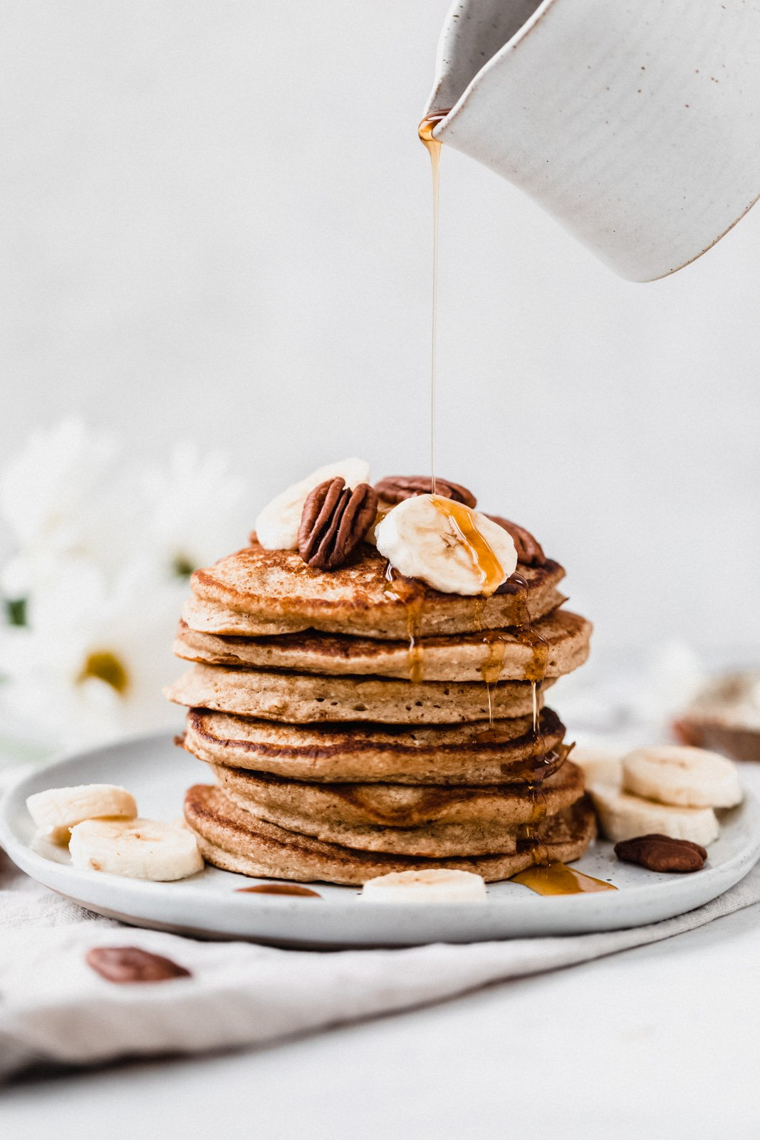 pouring syrup onto a stack of banana oatmeal pancakes