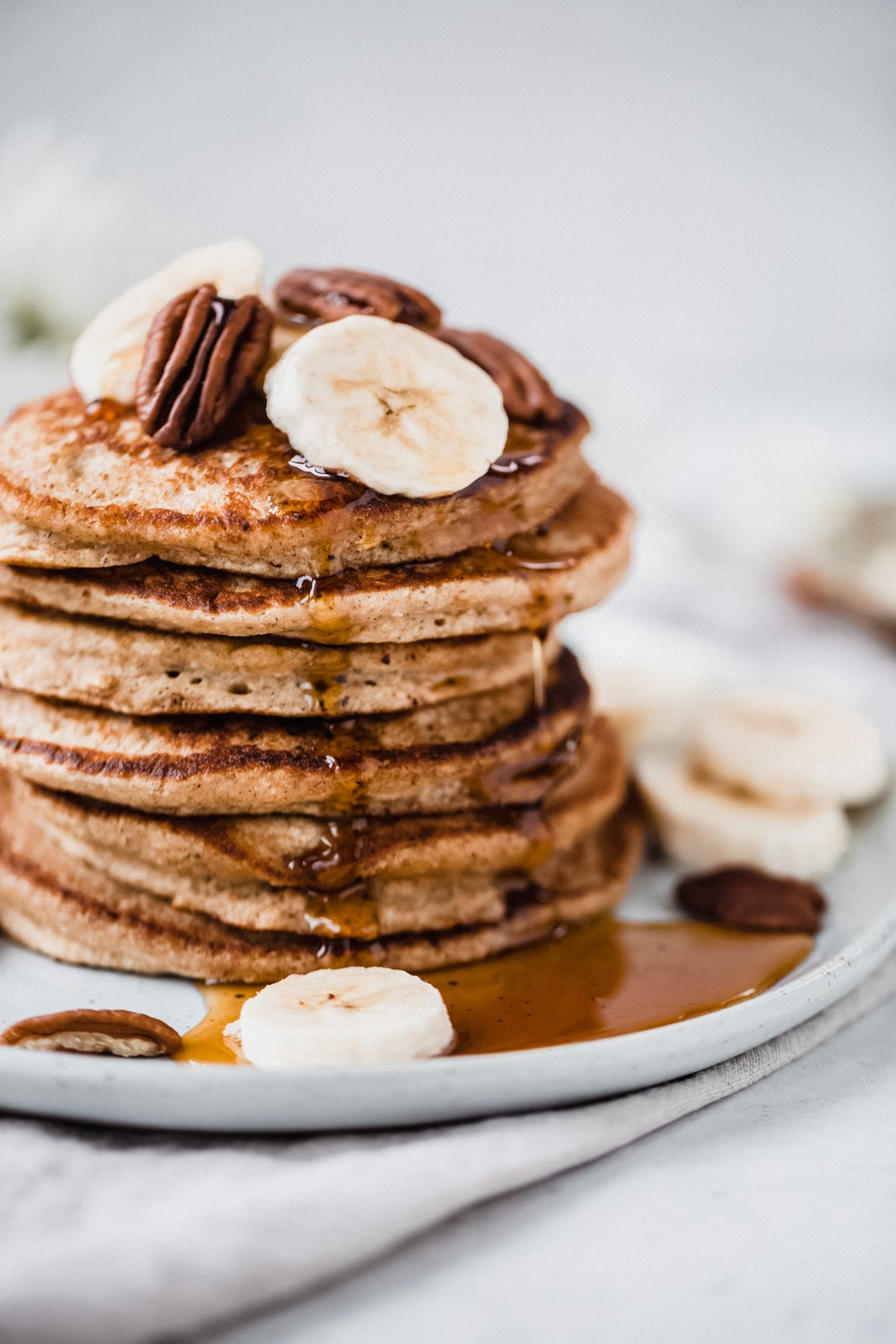 banana oatmeal pancakes in a stack on a plate topped with pecans and banana slices