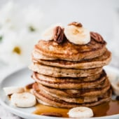 banana oatmeal pancakes stacked on a plate with maple syrup, banana slices and pecans