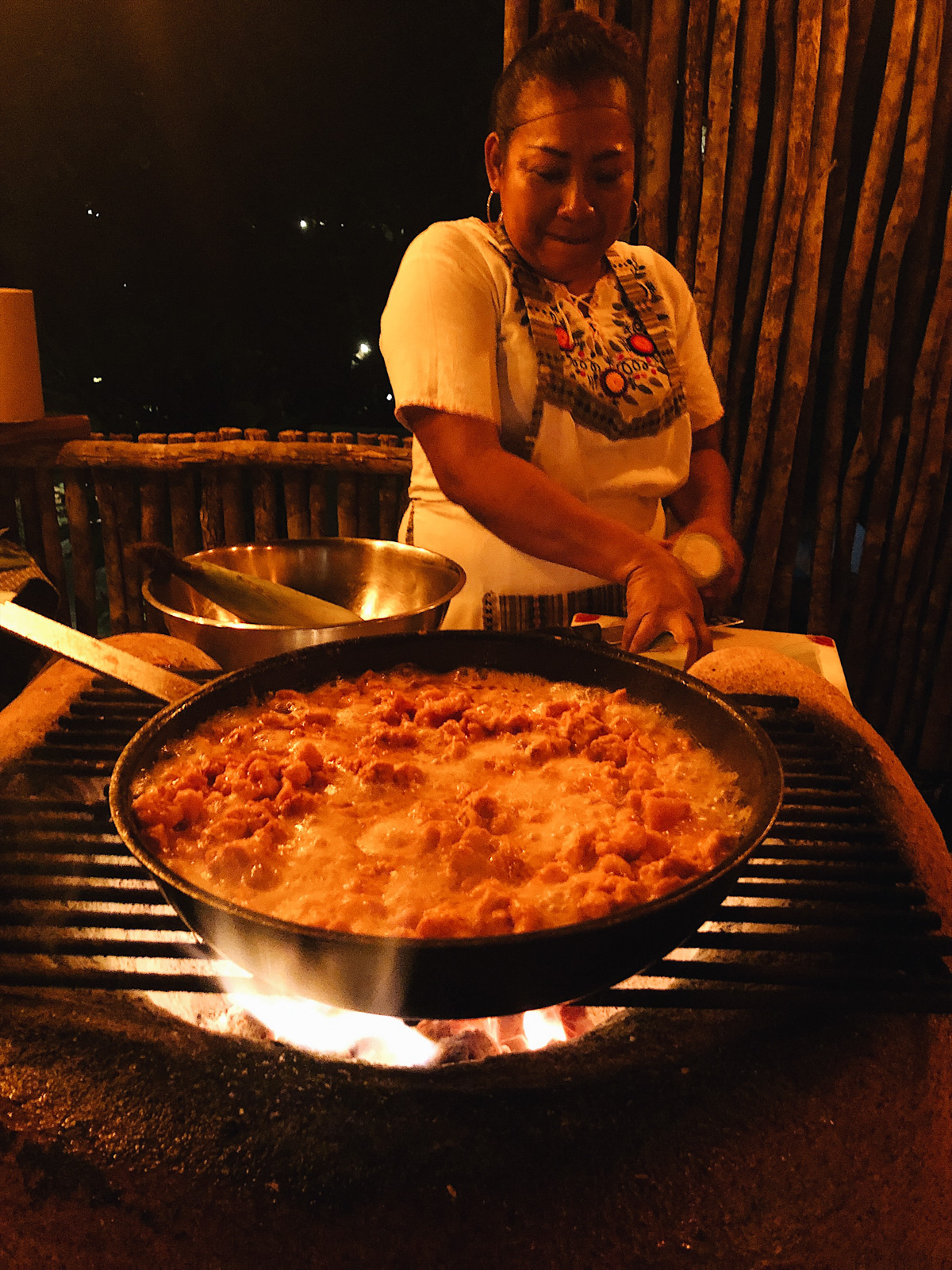woman cooking paella in a large pan over fire