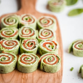 smoked salmon pinwheels on a wooden board