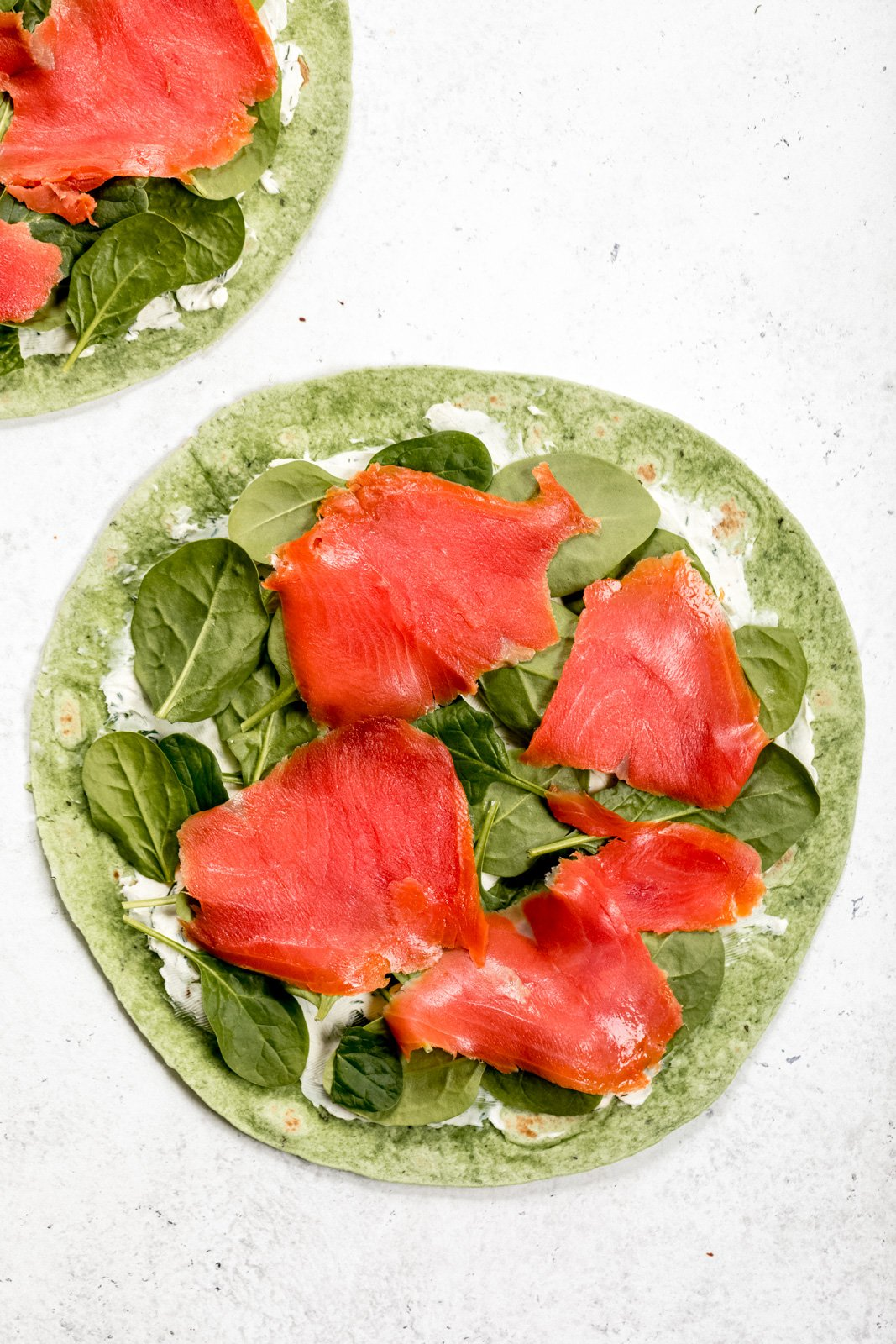 smoked salmon, spinach, and cream cheese on a spinach tortilla to make smoked salmon pinwheels