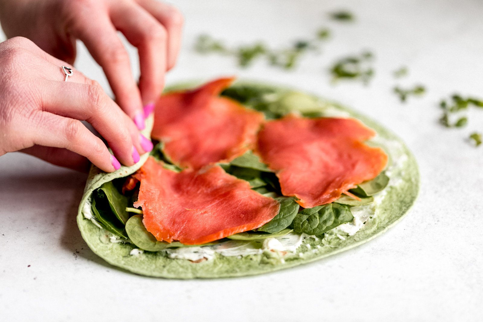 hands rolling up a spinach tortilla filled with ingredients to make smoked salmon pinwheels