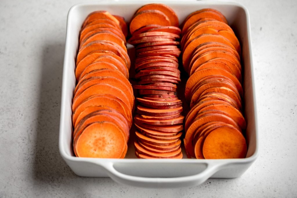 sweet potato slices in three lines in a white square baking dish