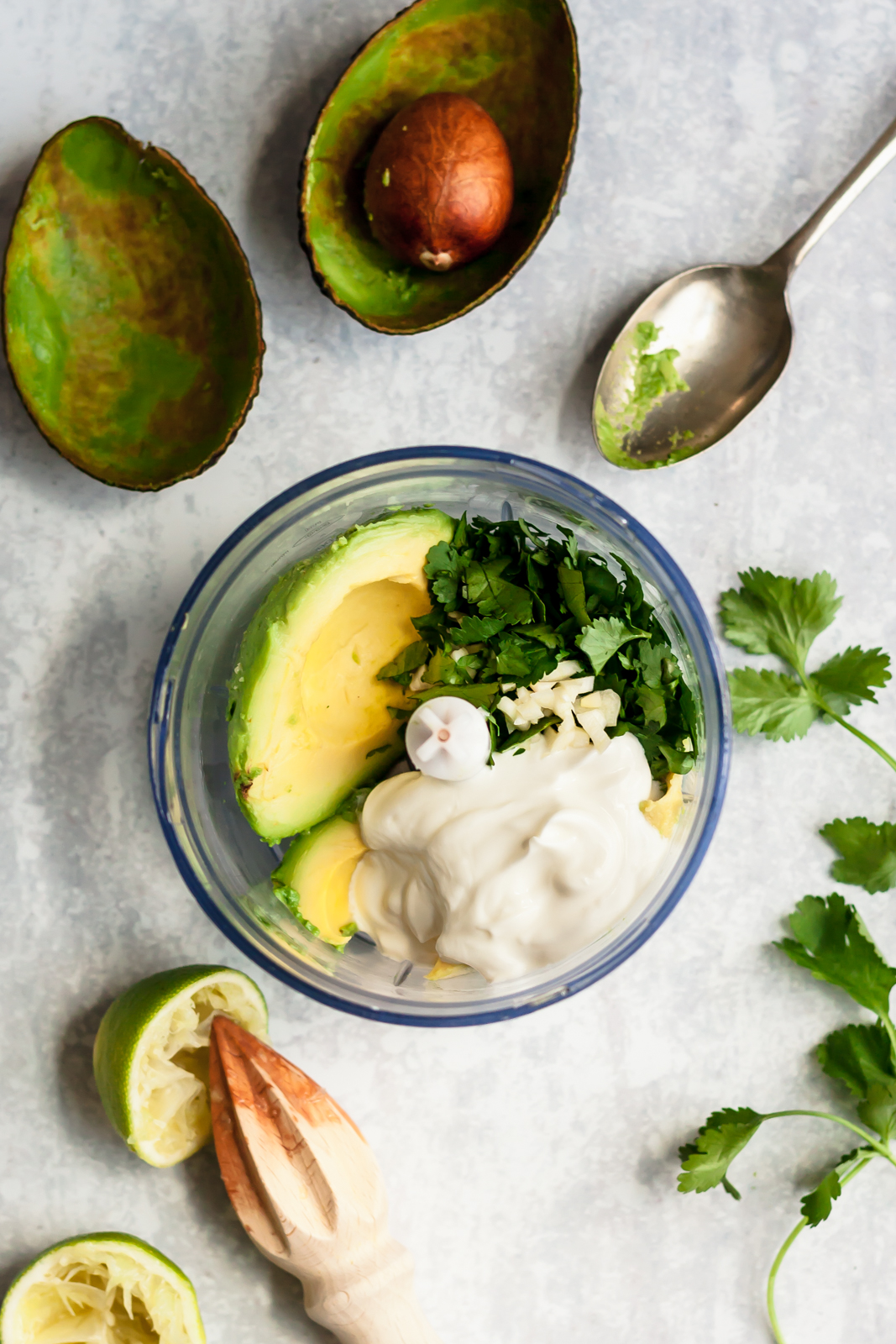 ingredients for avocado lime sauce in the bowl of a food processor