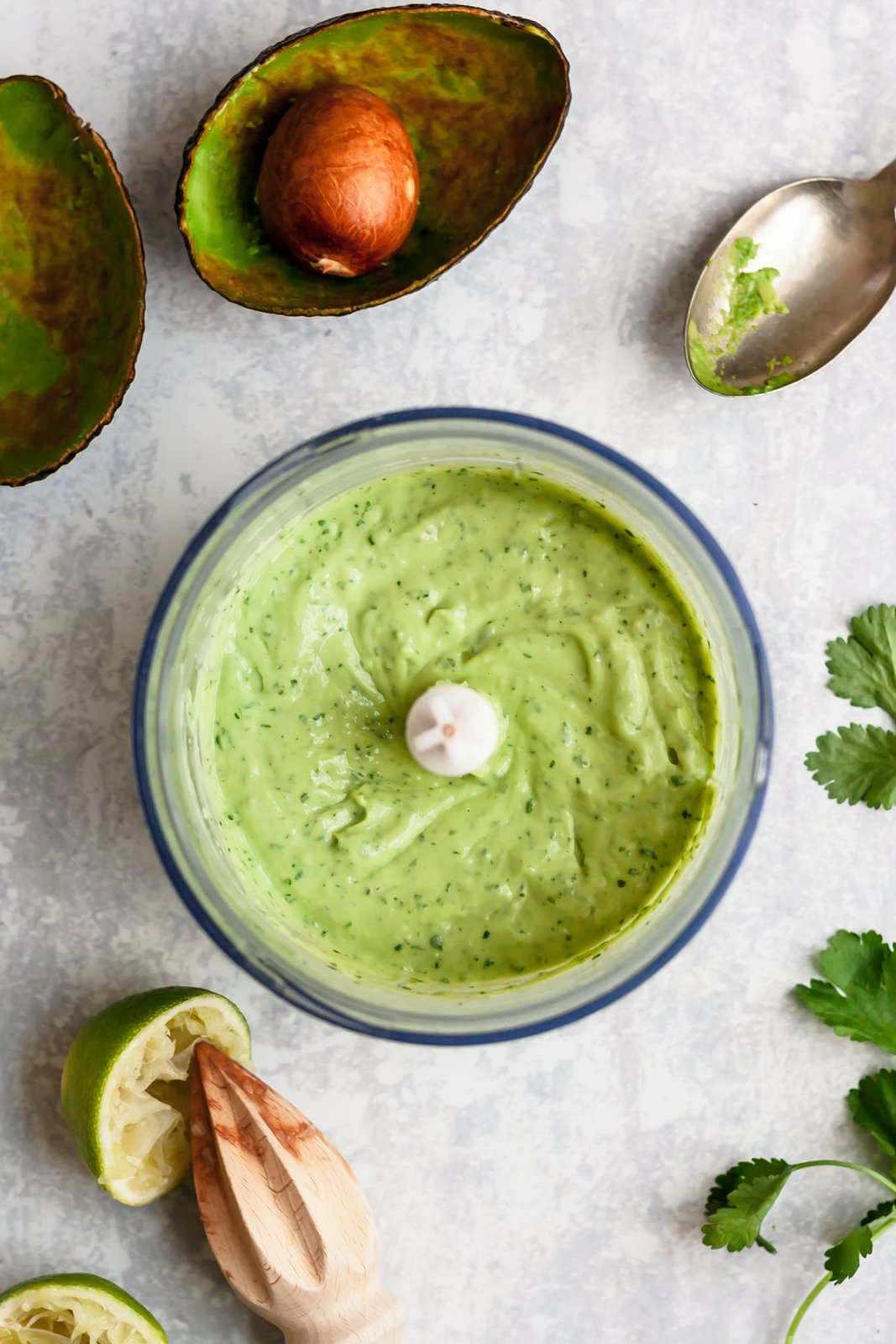 avocado lime sauce in the bowl of a food processor with ingredients around it