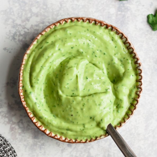 avocado lime sauce in a bowl with a spoon