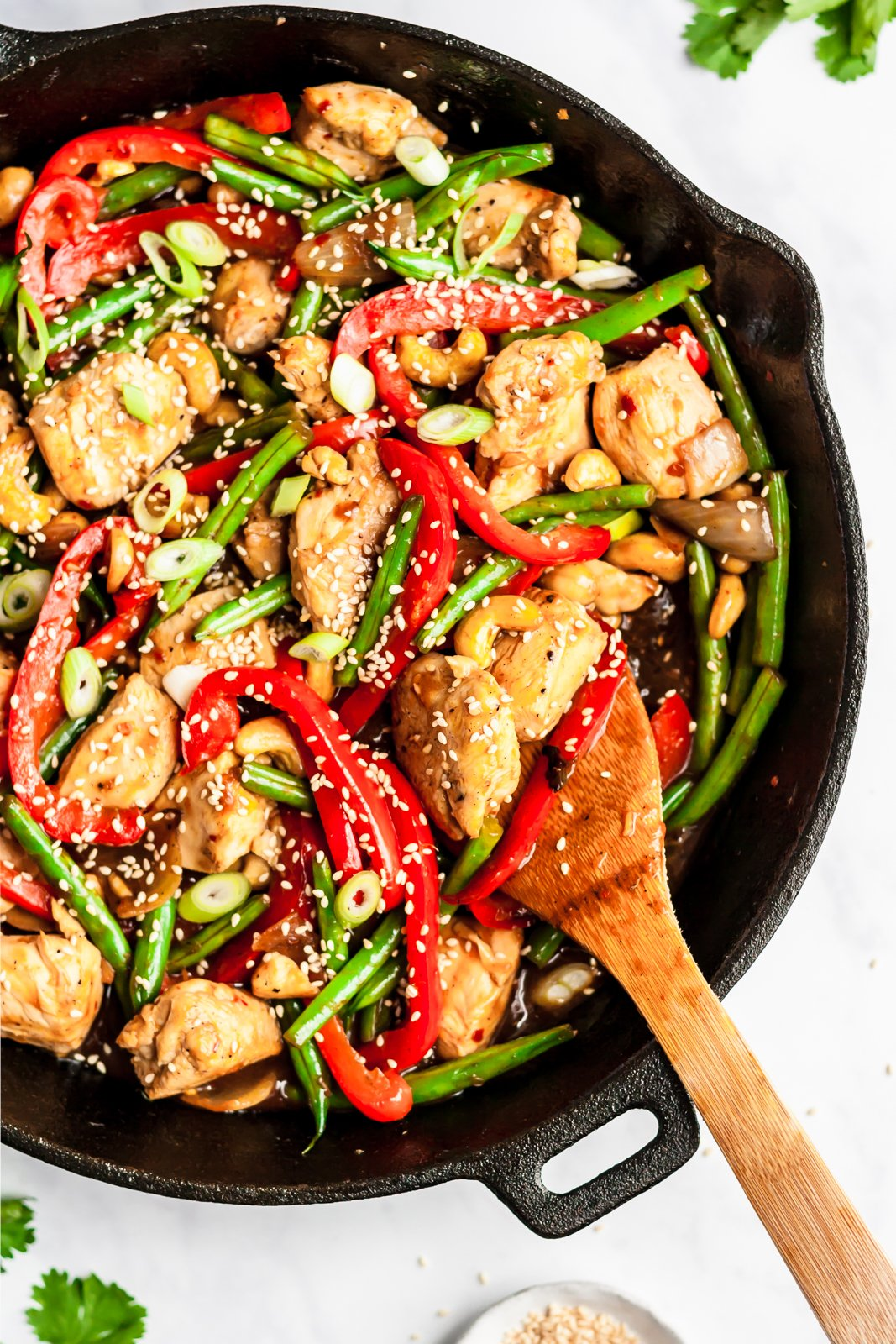 orange chicken stir fry in a skillet pan with a wooden spoon