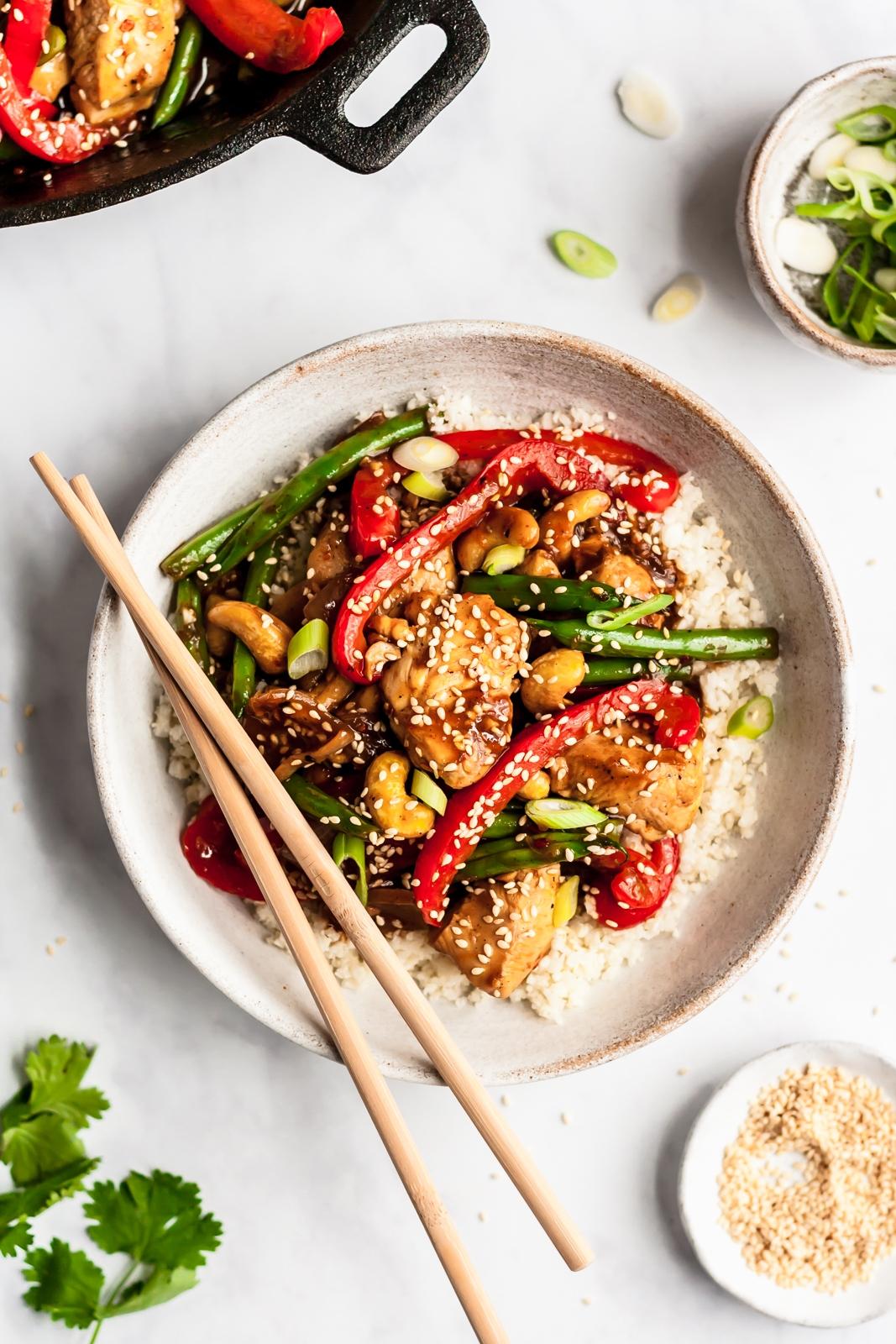 healthy orange chicken stir fry in a bowl over cauliflower rice