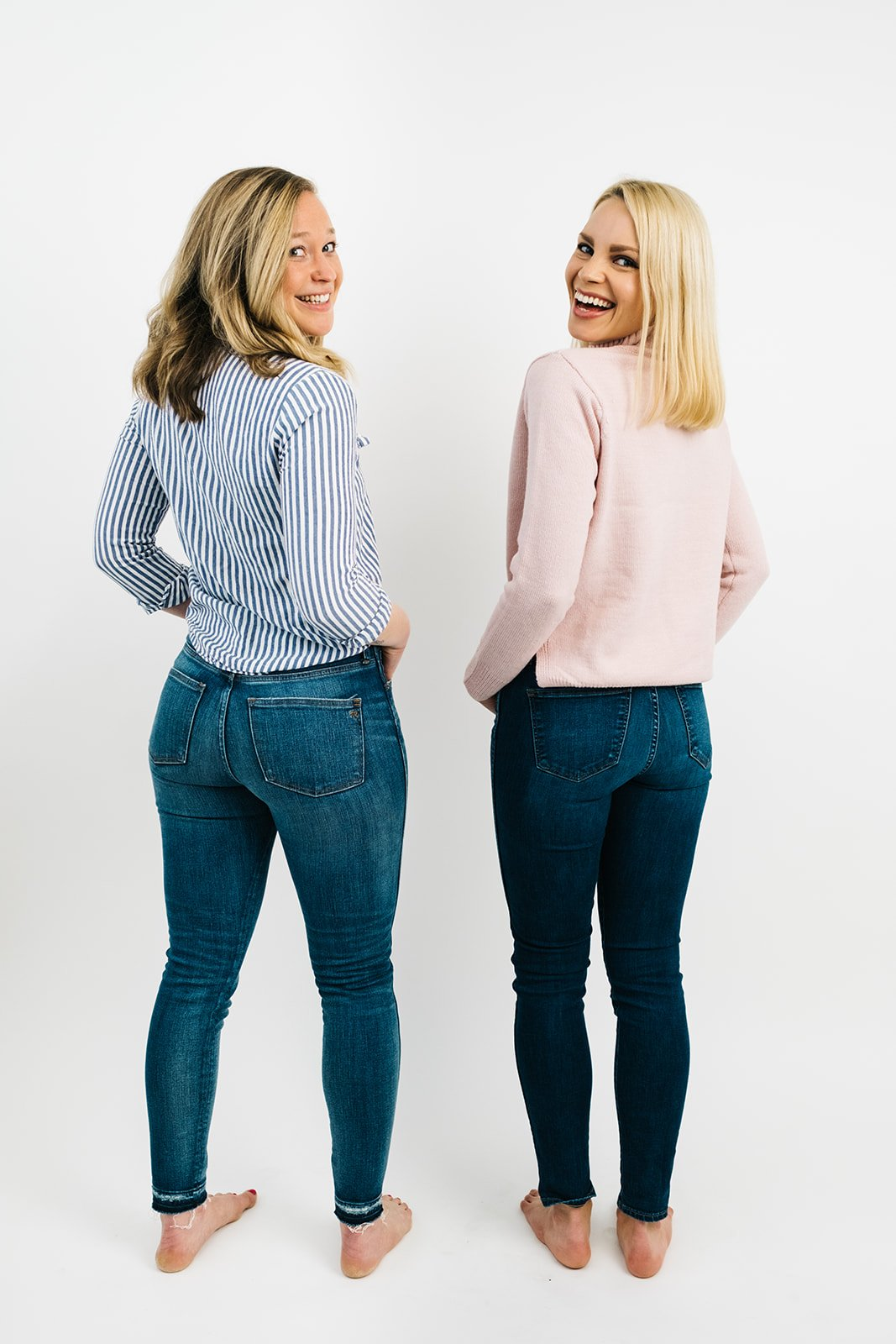 two blonde women in jeans and long sleeved shirts looking over their shoulders