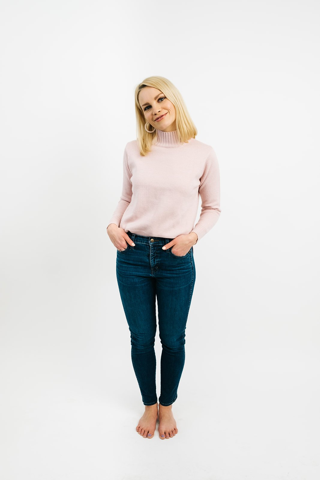 blonde woman in jeans and a light pink turtleneck