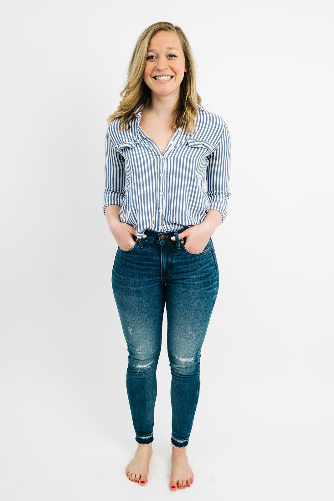 blonde woman in jeans and a blue striped button down shirt