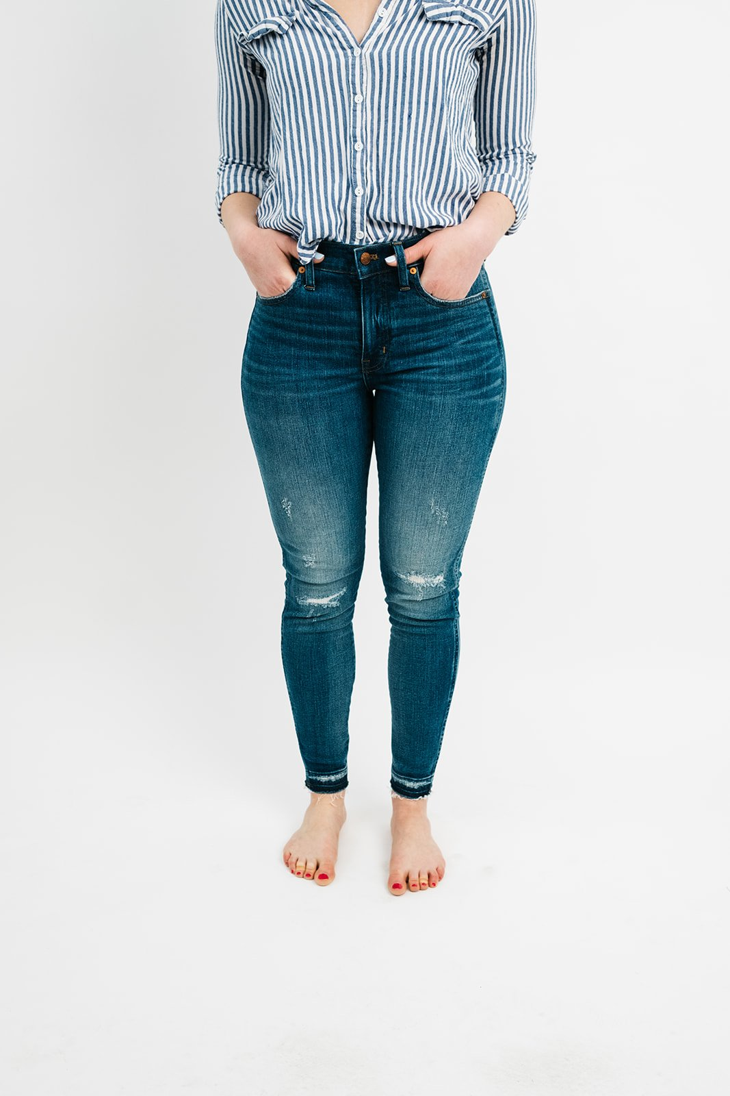 bottom half of a woman in jeans and a blue striped shirt