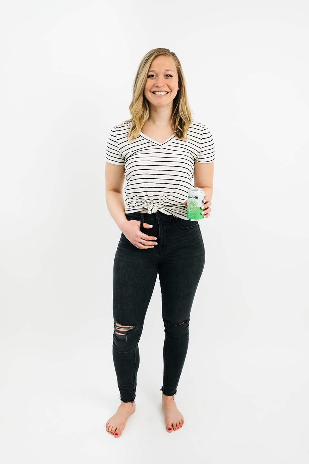 blonde woman in black jeans and a striped t-shirt holding a can