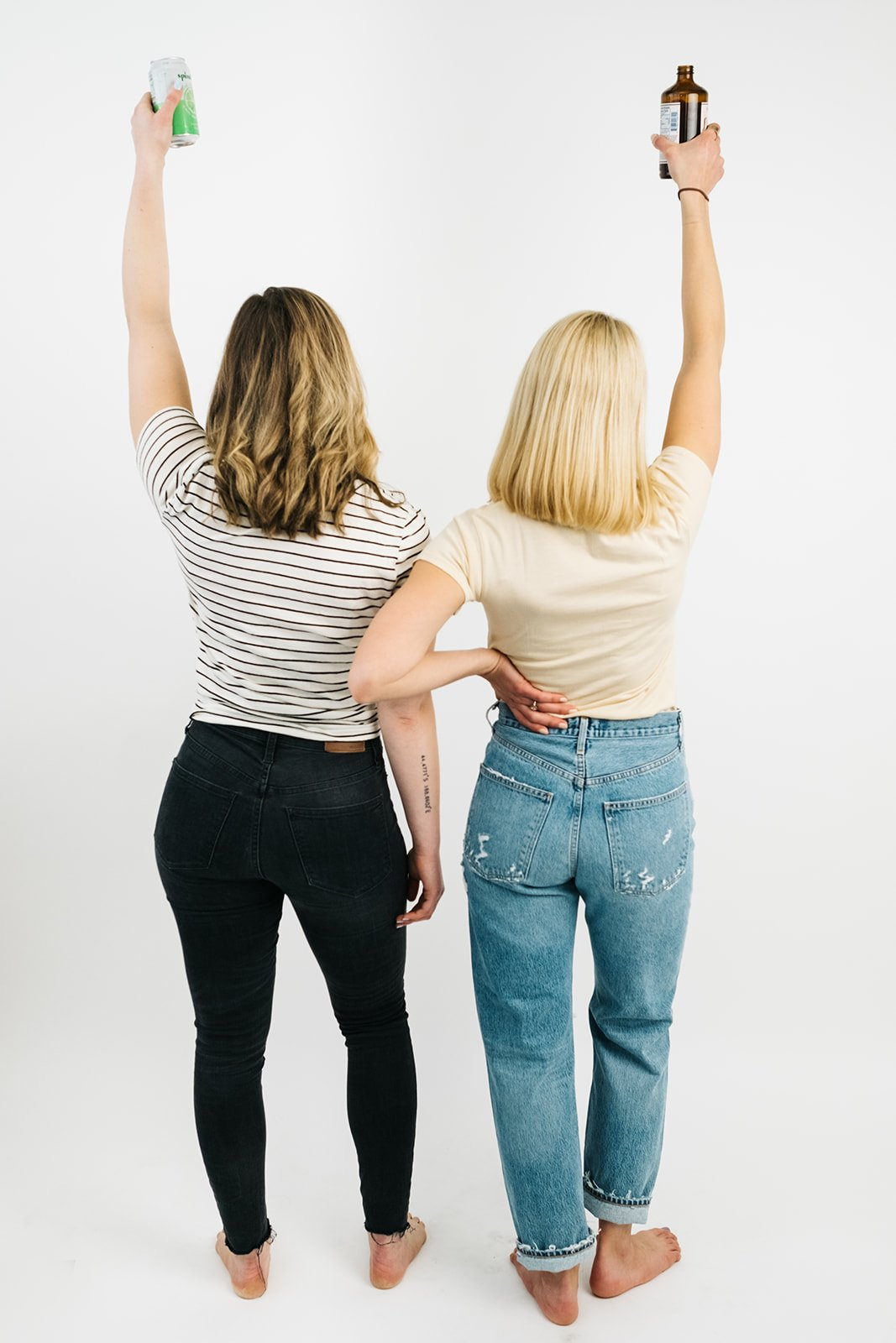 the back of two women in jeans and t-shirts holding drinks in the air