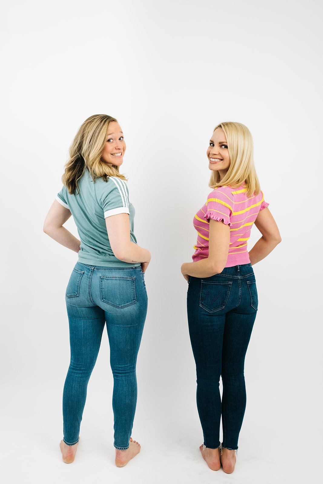 two blonde women in jeans and t-shirts looking over their shoulders