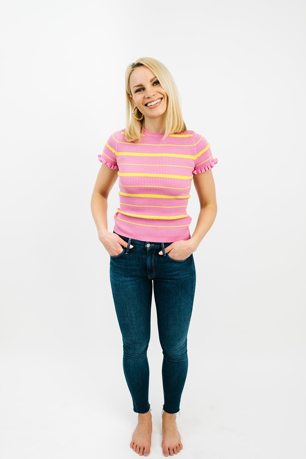 blonde woman in jeans and a pink striped t-shirt