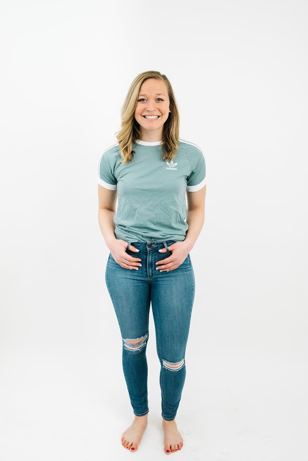 blonde woman in ripped jeans and a green t-shirt