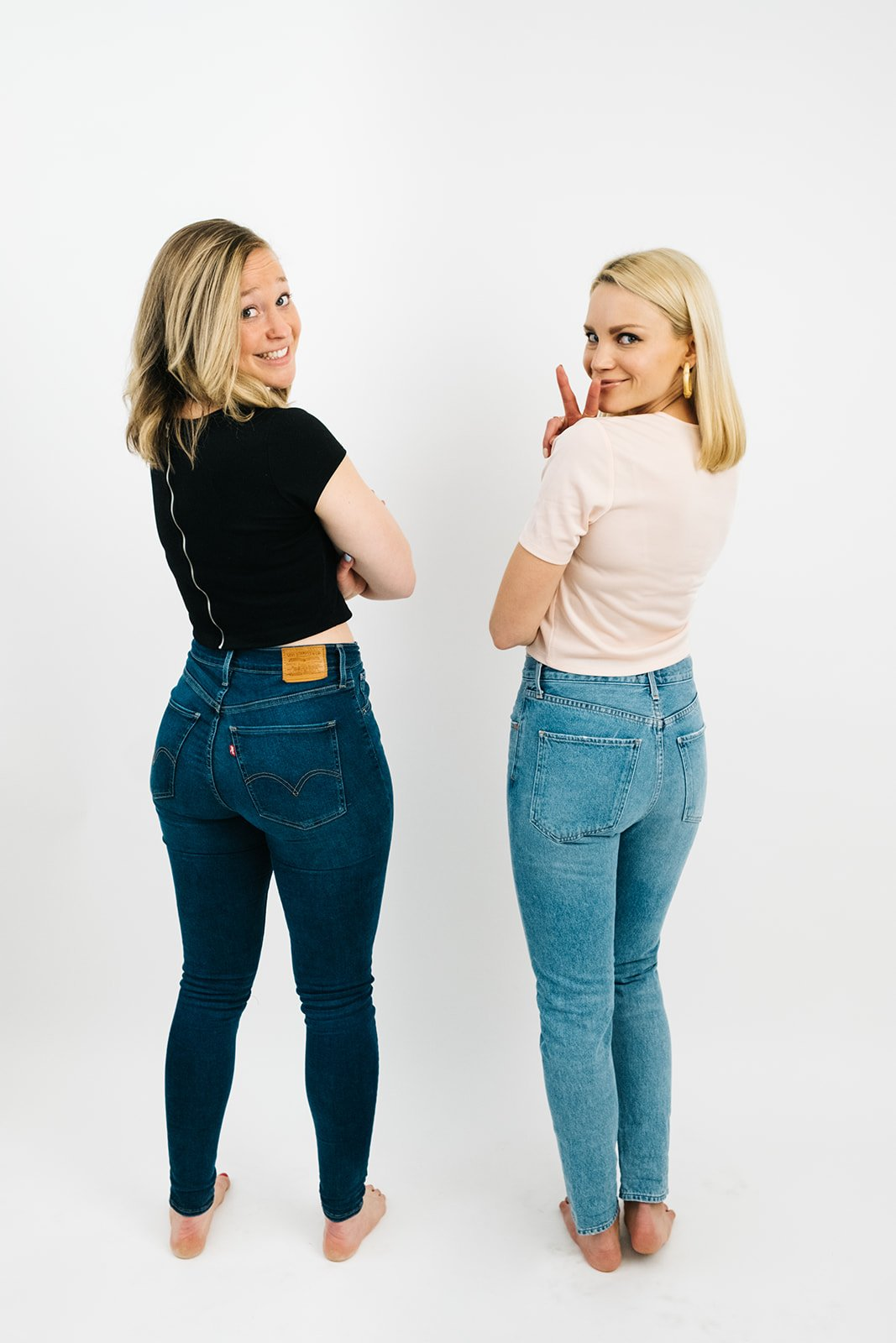 two women in jeans and t-shirts looking over their shoulders