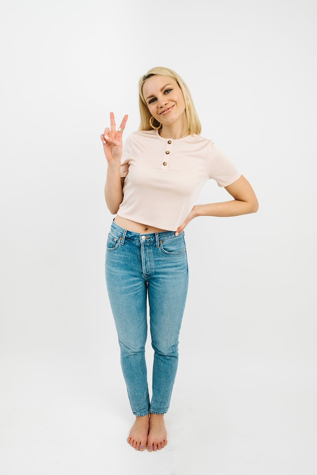 blonde woman in light washed jeans and a light pink t-shirt with buttons