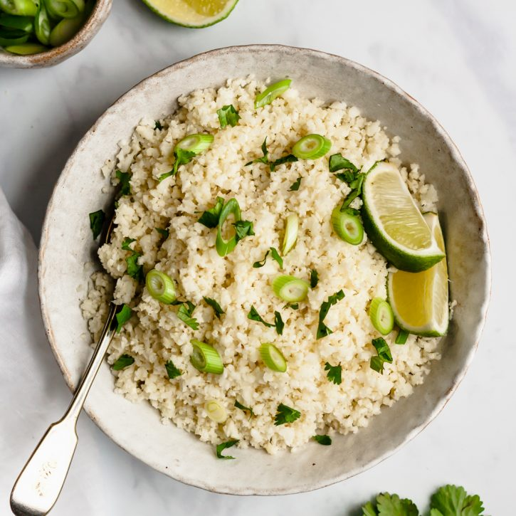 bowl of cauliflower rice topped with scallions and lime wedges