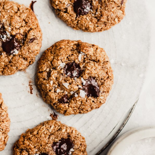healthy oatmeal chocolate chip cookies on a cooling rack with sea salt on the side
