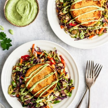 two sweet potato salmon cakes on two plates with salad and green dressing on the side