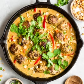 cilantro chicken meatballs in a skillet with mango coconut sauce