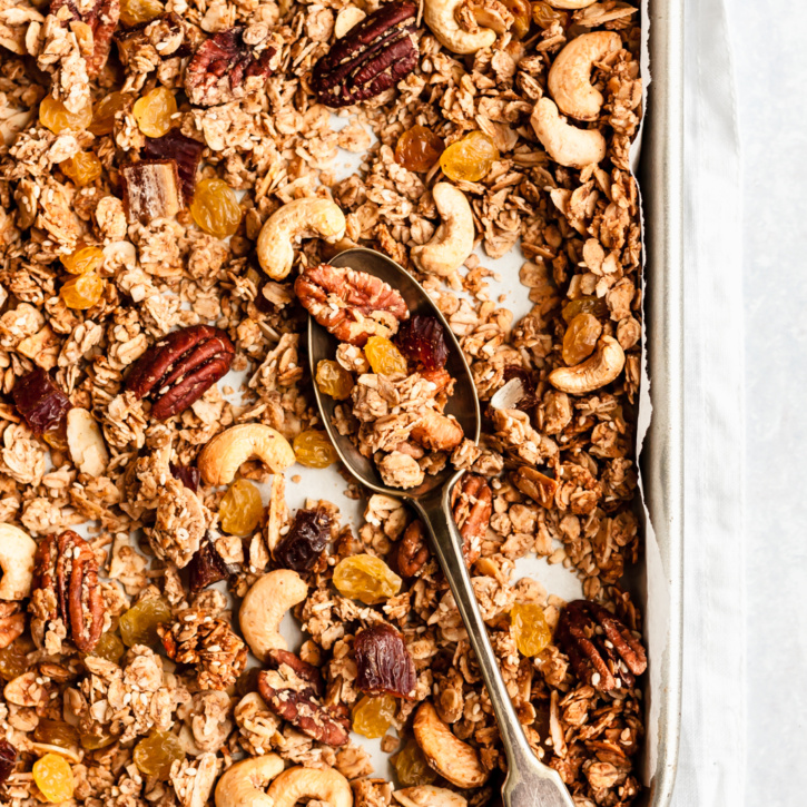 homemade chunky healthy granola on a baking sheet with a spoon