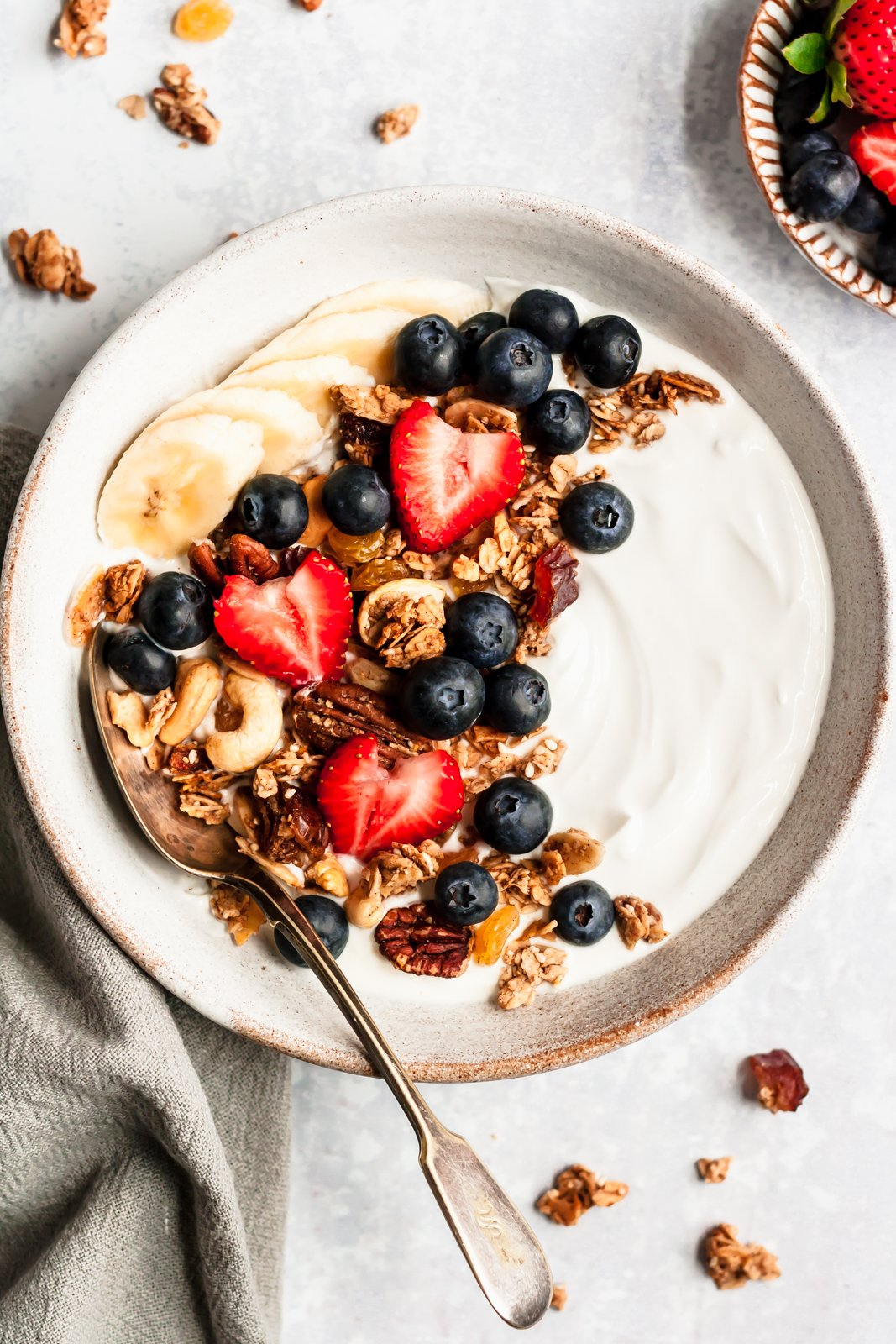 yogurt in a bowl topped with healthy granola, berries and bananas