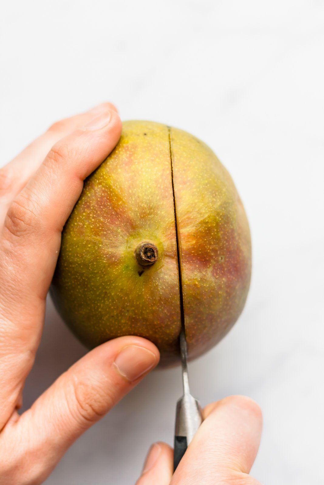 cutting a mango with a knife