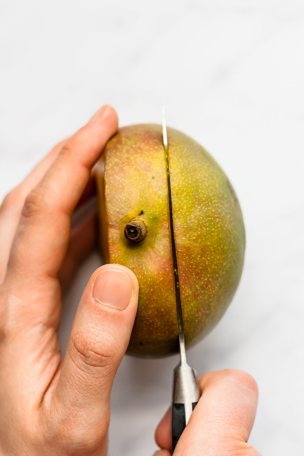 cutting half of a mango with a knife