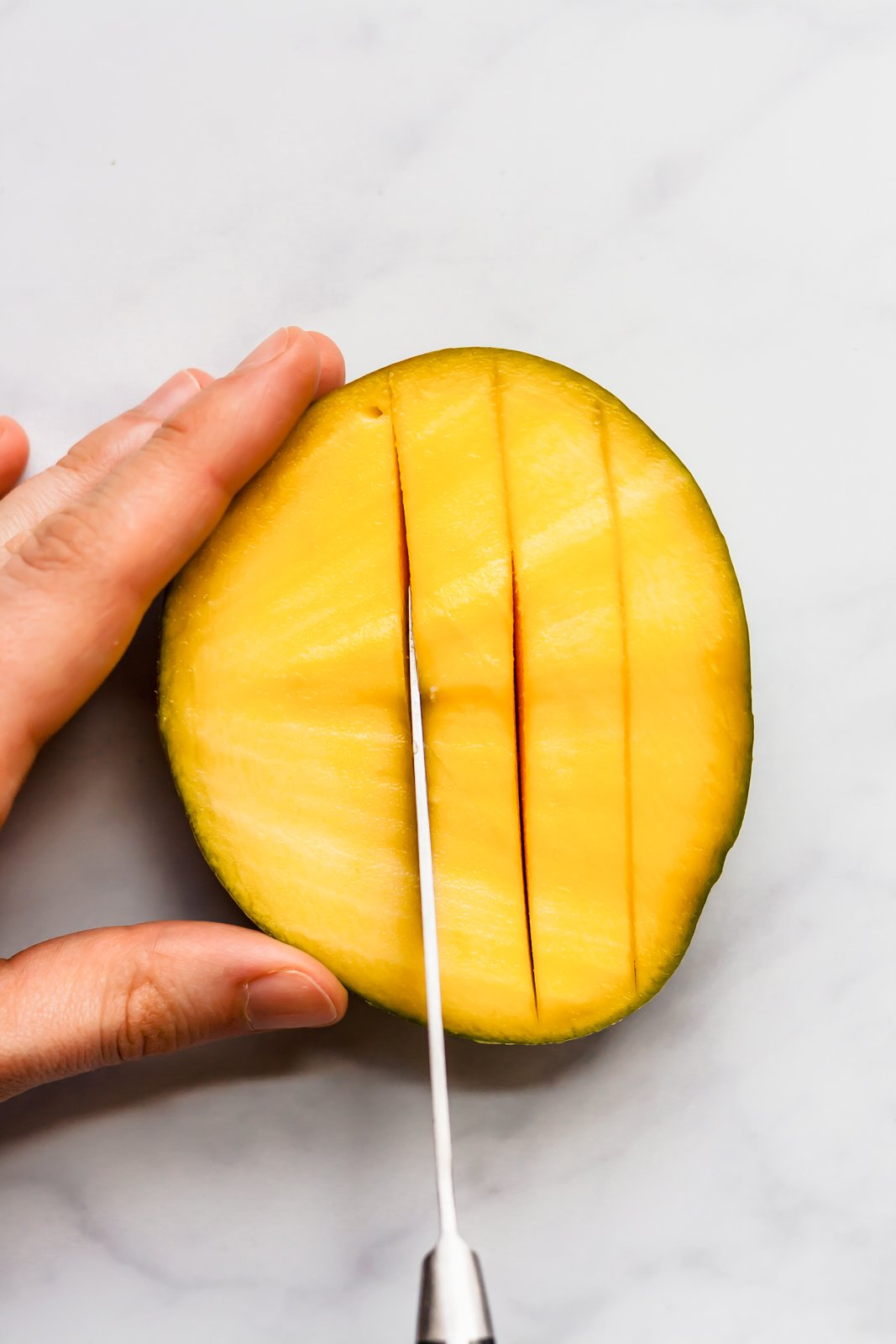 cutting half of a mango into slices