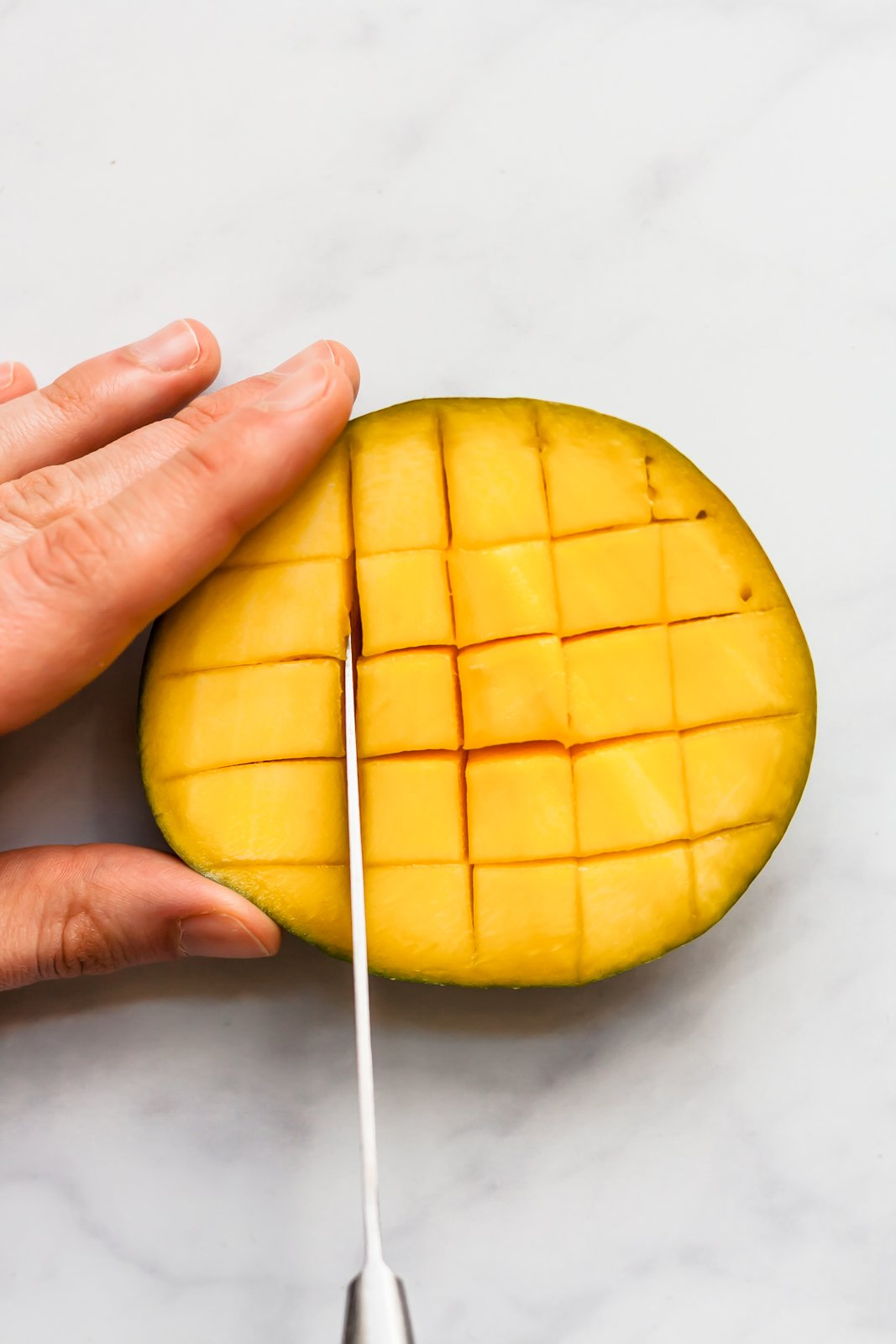 cutting half of a mango into cubes