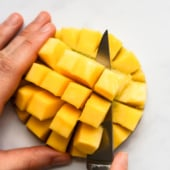 cutting mango cubes off of half of a mango