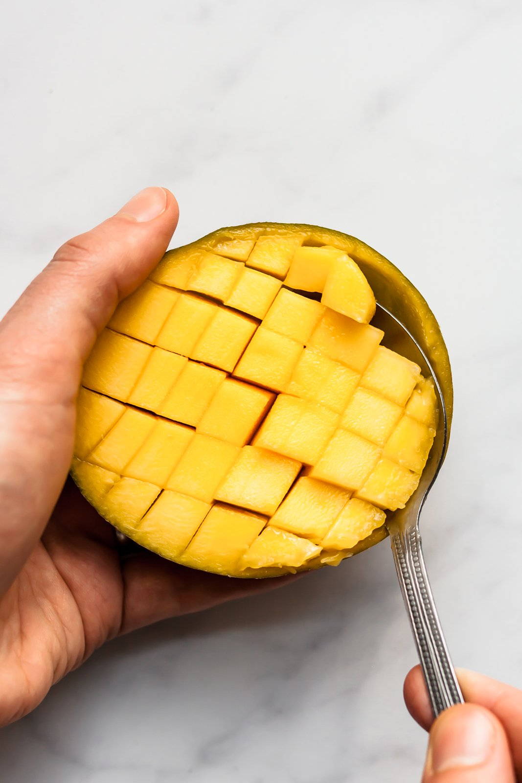 scooping mango cubes out of half of a mango