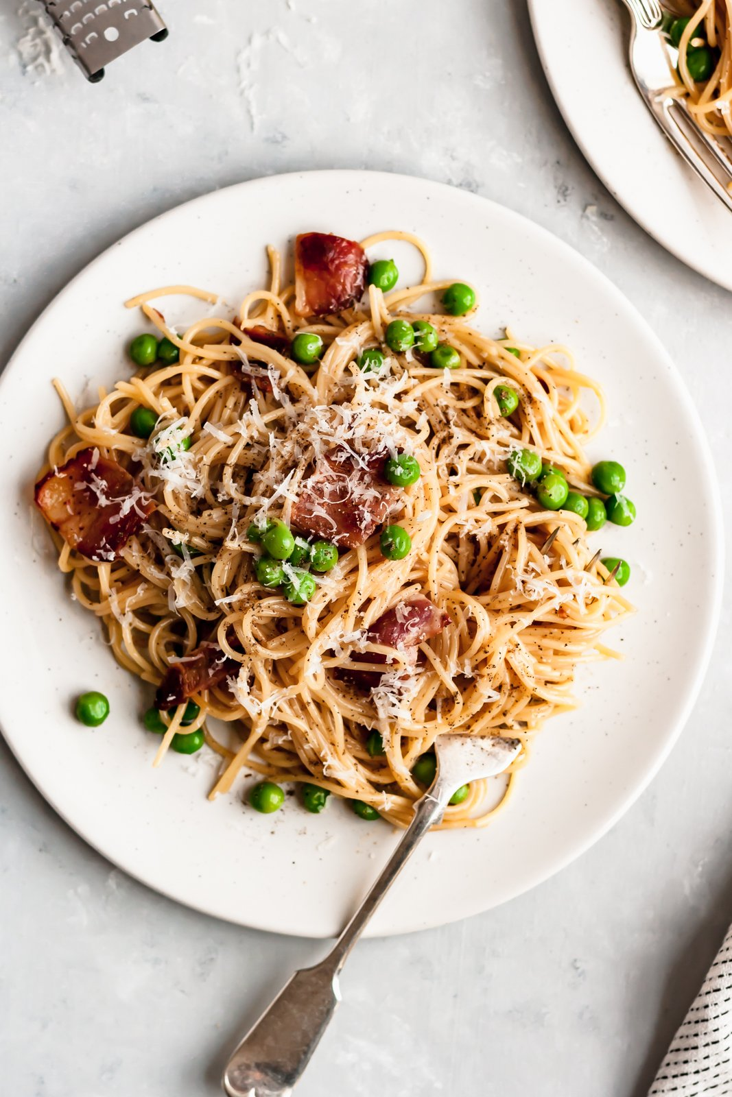 healthy pasta carbonara with peas on a plate with a fork