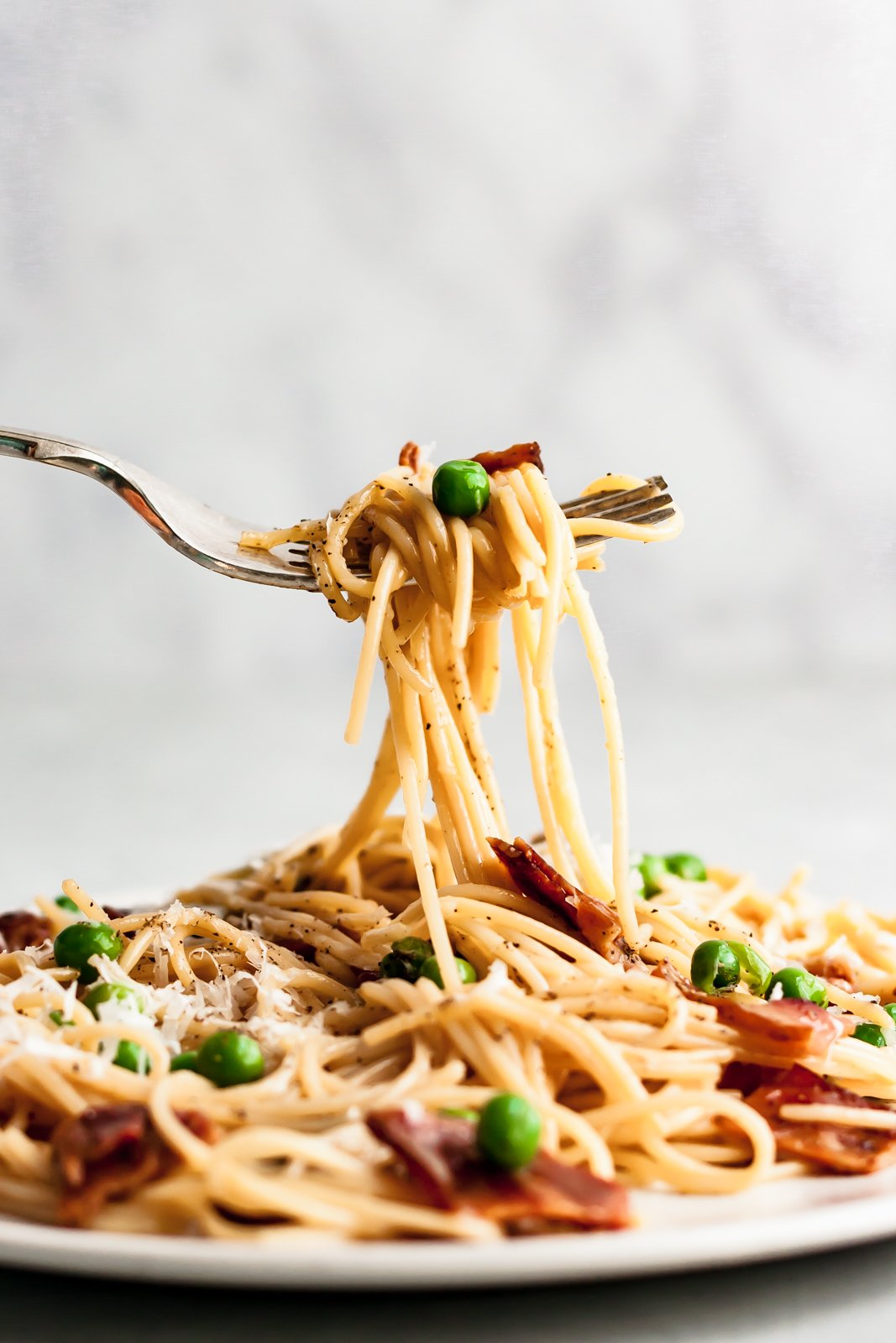 fork pulling up healthy pasta carbonara with peas