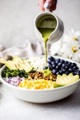 cilantro lime dressing being poured over a quinoa salad with avocado