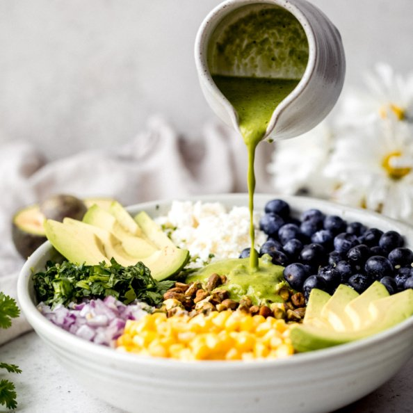 pouring homemade cilantro lime dressing onto a salad with corn, avocado, quinoa and blueberries