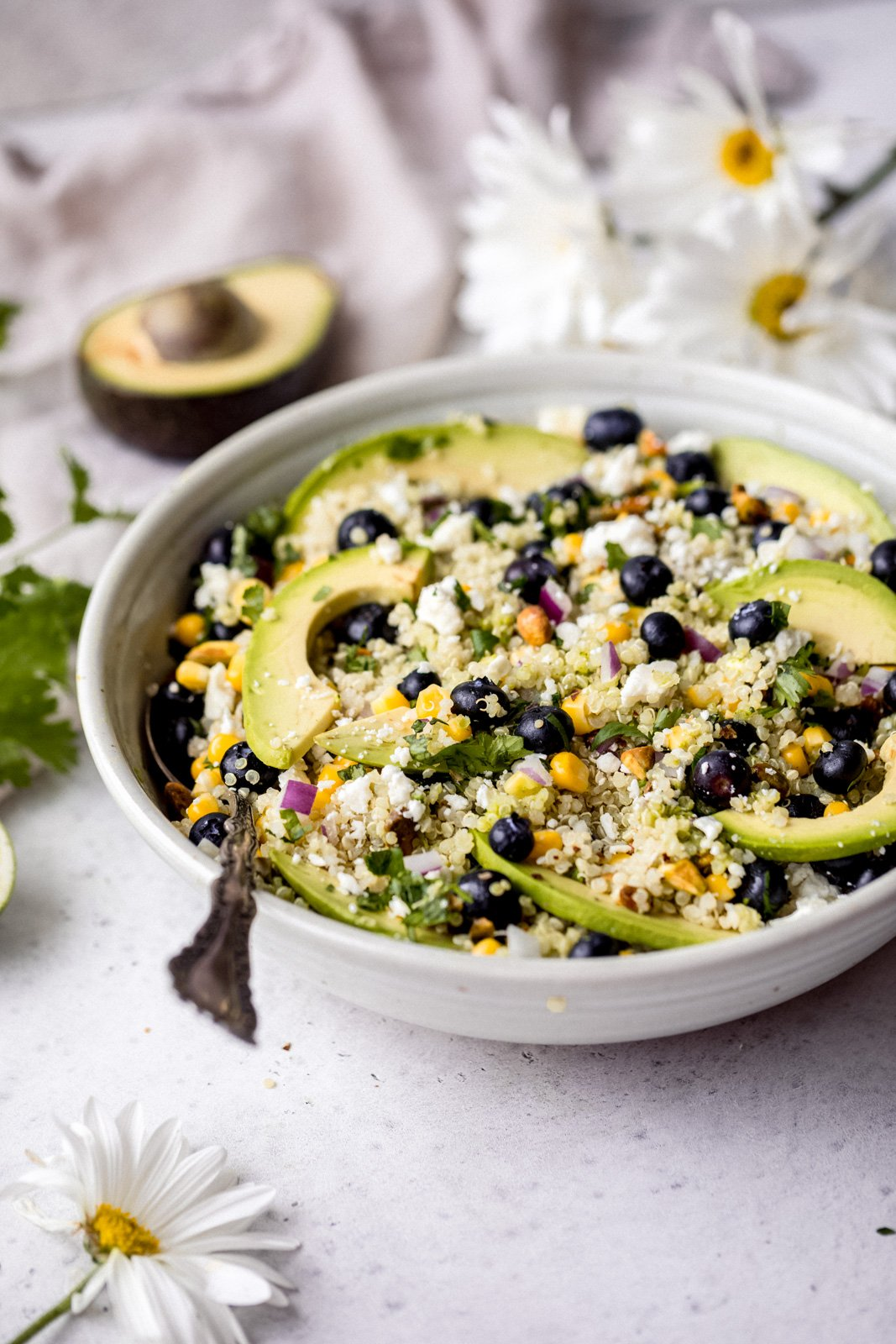 avocado blueberry salad in a bowl with a spoon