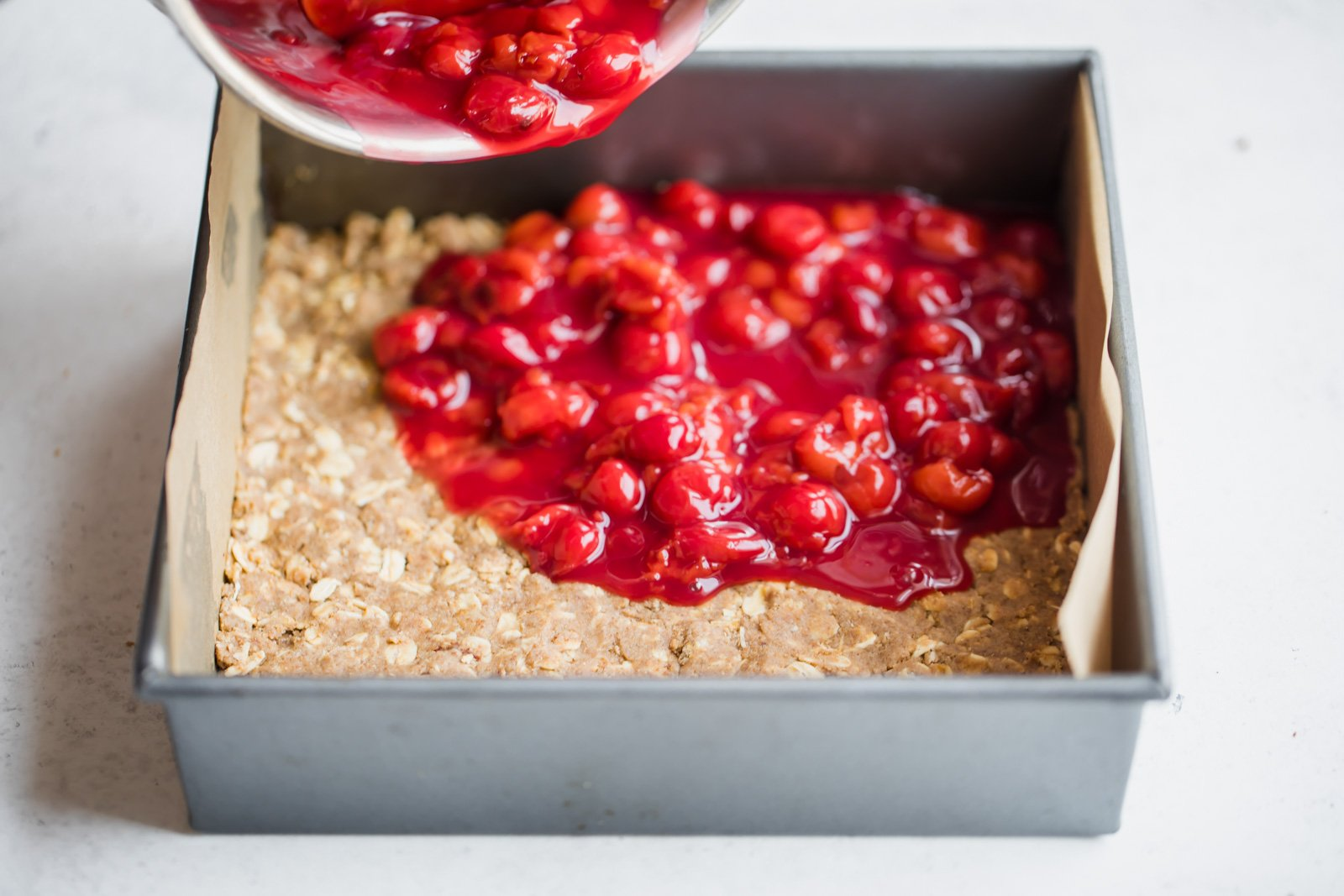 tart cherry pie filling being poured onto crust in a square pan