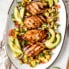 chicken breasts on a platter with avocado slices, red onion, and pico de gallo