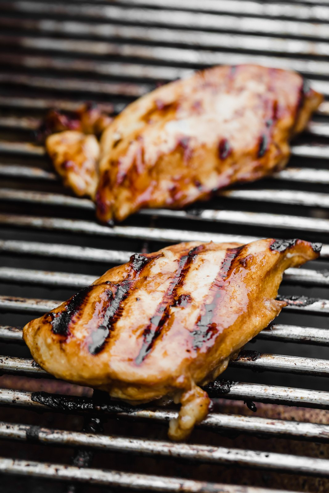 two chicken breasts on a grill