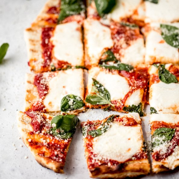 grilled pizza with cheese, tomato sauce, and basil cut into 16 squares